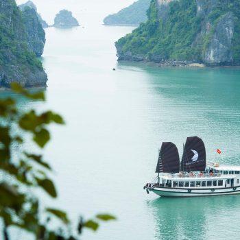 Boat Sailing in Halong Bay near huge cliffs