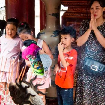 Vietnamese people praying in a temple